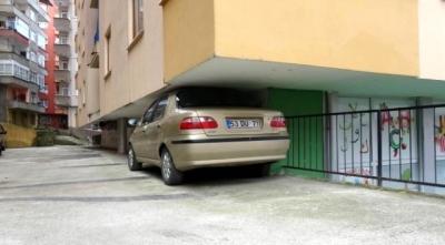 RİZE'de şoför emeklisi 70 yaşındaki Zikrullah Subaşı, yol yapım çalışması nedeniyle binanın otoparkına ulaşamayınca aracı, altına güçlükle sığdığı bir binanın giriş katındaki balkonun altına park etti.